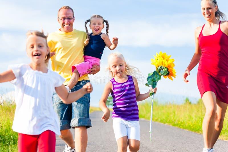 Familia con el funcionamiento de tres niños imagen de archivo libre de regalías