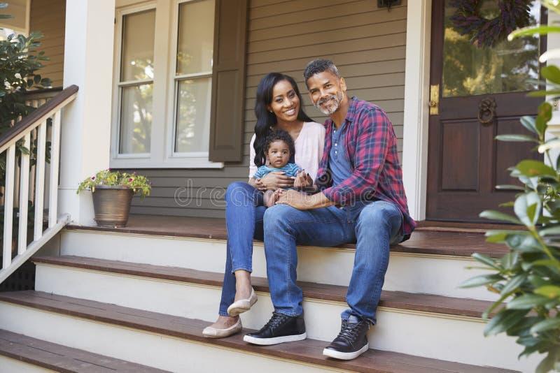 Familia con el hijo Sit On Steps Leading Up del bebé al pórtico del hogar foto de archivo libre de regalías