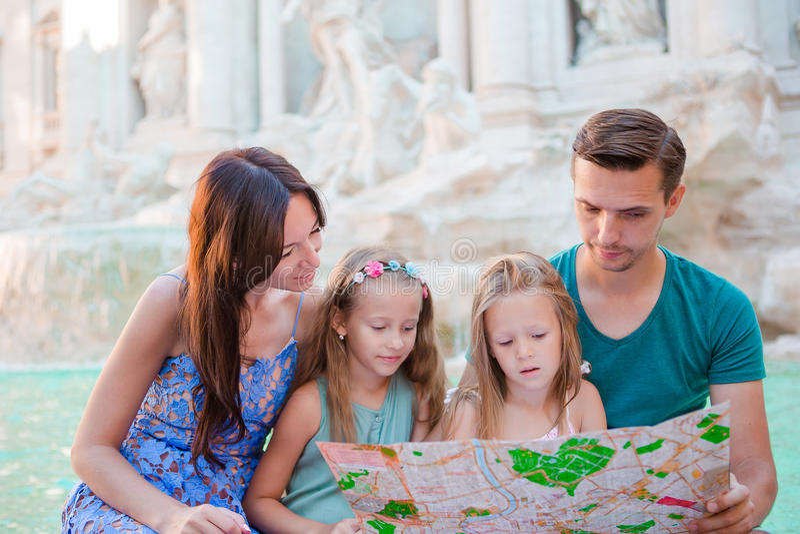 Familia con el mapa turístico cerca de Fontana di Trevi, Roma, Italia El padre y los niños felices disfrutan de día de fiesta ita imagenes de archivo