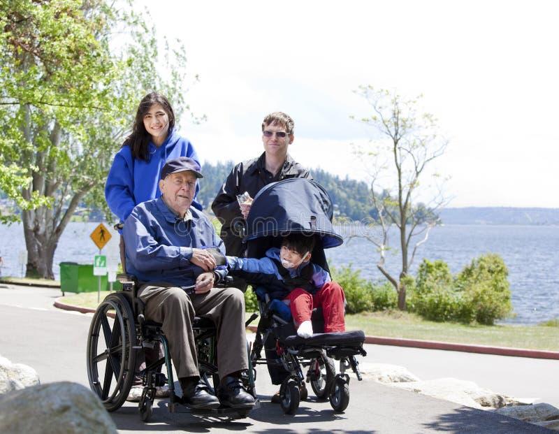 Familia con el mayor y el niño lisiados al aire libre fotos de archivo libres de regalías