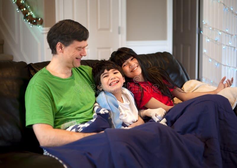 Familia con el muchacho discapacitado que se relaja junto en el sofá de cuero foto de archivo