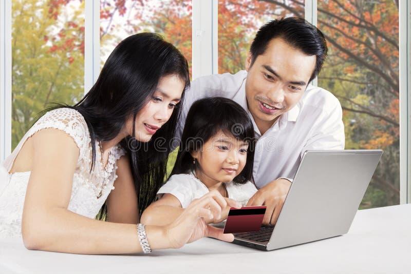 Familia con el ordenador portátil y la tarjeta de crédito foto de archivo libre de regalías