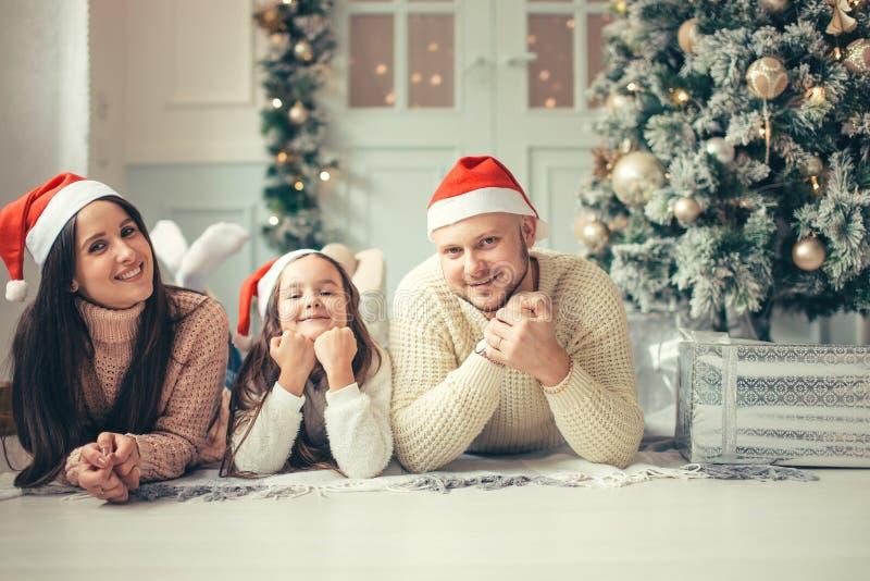 Familia con el sombrero de Papá Noel que miente cerca del árbol de navidad, concepto de la celebración del día de fiesta imágenes de archivo libres de regalías