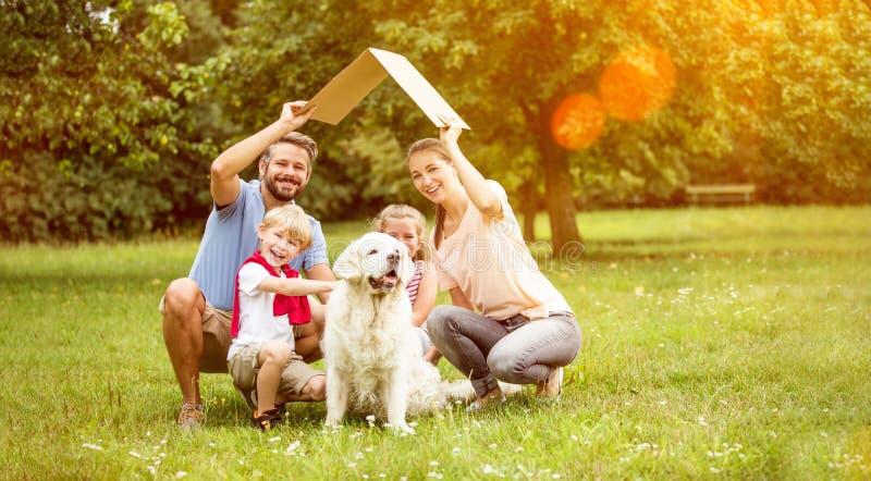 Familia con el tejado como concepto de la construcción de la casa imagen de archivo libre de regalías