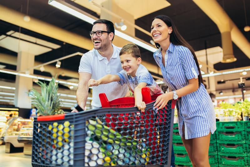 Familia con la comida de compra del niño y del carro de la compra en el colmado o el supermercado imagenes de archivo