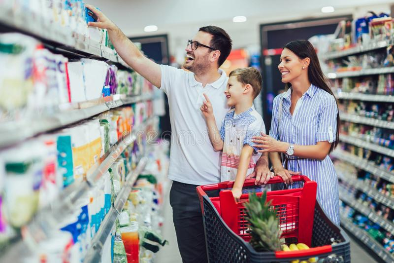 Familia con la comida de compra del niño y del carro de la compra en el colmado o el supermercado fotos de archivo libres de regalías