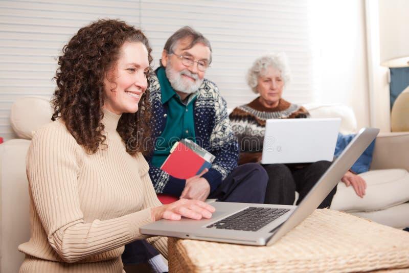 Familia con la computadora portátil fotografía de archivo