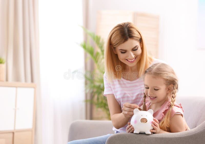 Familia con la hucha y el dinero en casa fotos de archivo libres de regalías