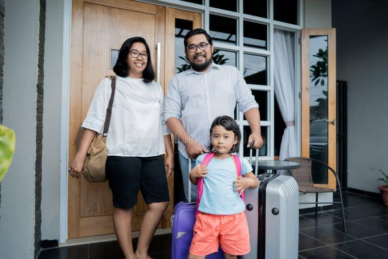 Familia con la maleta que se coloca delante de su casa fotografía de archivo