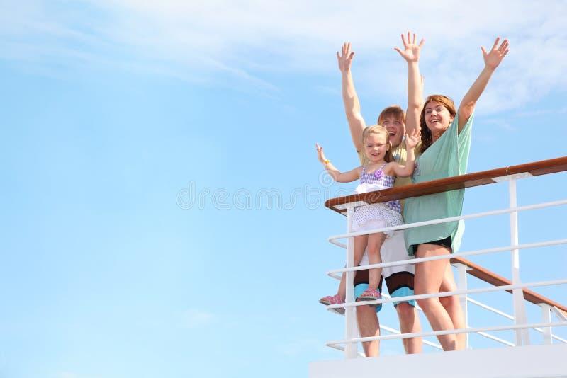 Familia con la muchacha con las manos para arriba, restos en el yate fotografía de archivo libre de regalías