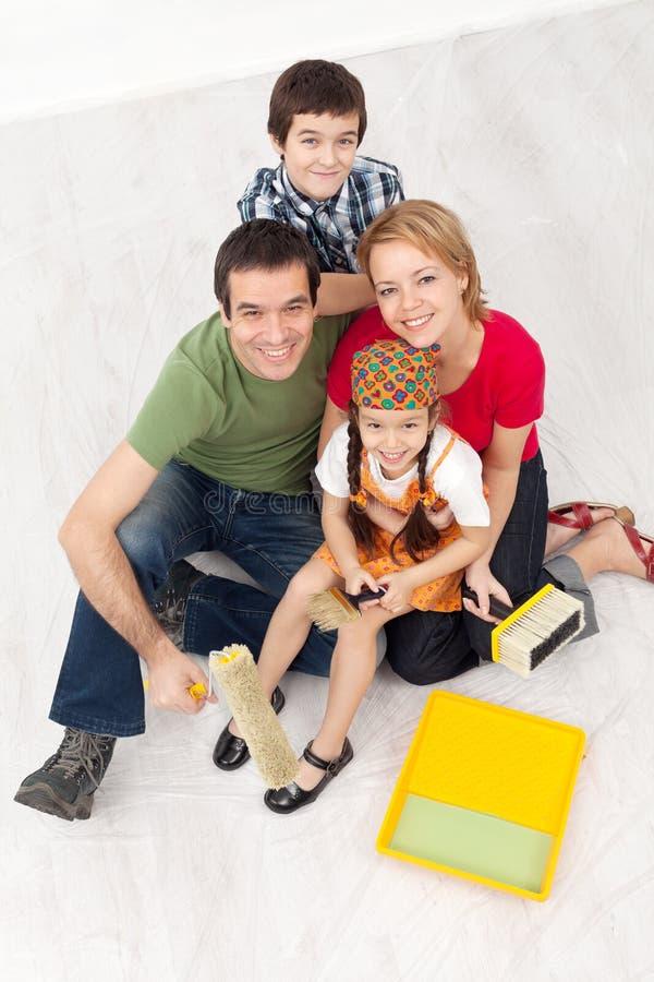 Familia con la pintura que se prepara para redecorate su hogar imagenes de archivo