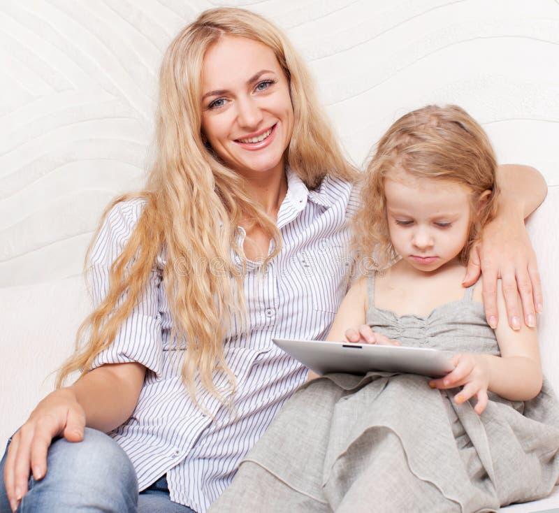 Familia con la tableta en el sofá foto de archivo