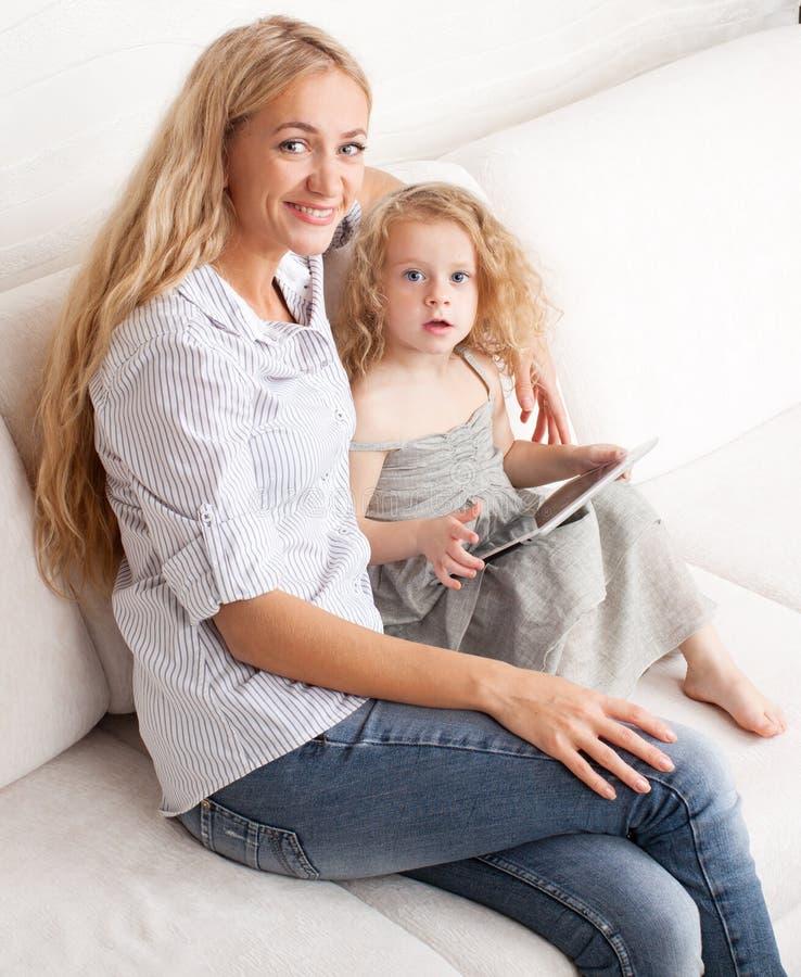Familia con la tableta en el sofá fotos de archivo libres de regalías