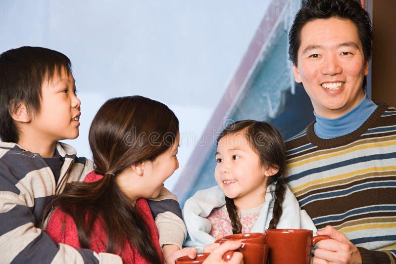 Familia con las bebidas calientes imagen de archivo