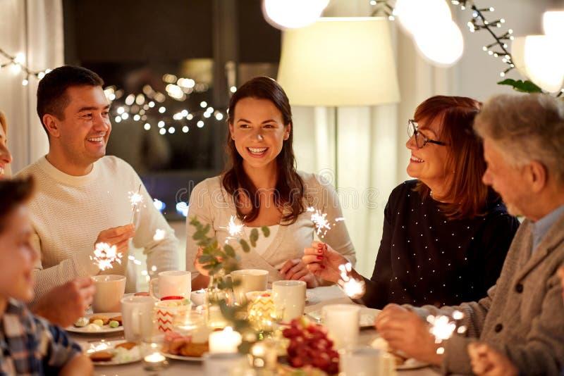 Familia con las bengalas que tienen la fiesta del t? en casa imagenes de archivo