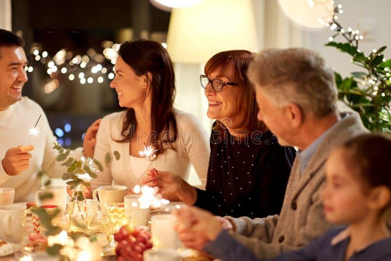 Familia con las bengalas que tienen la fiesta del t? en casa fotos de archivo