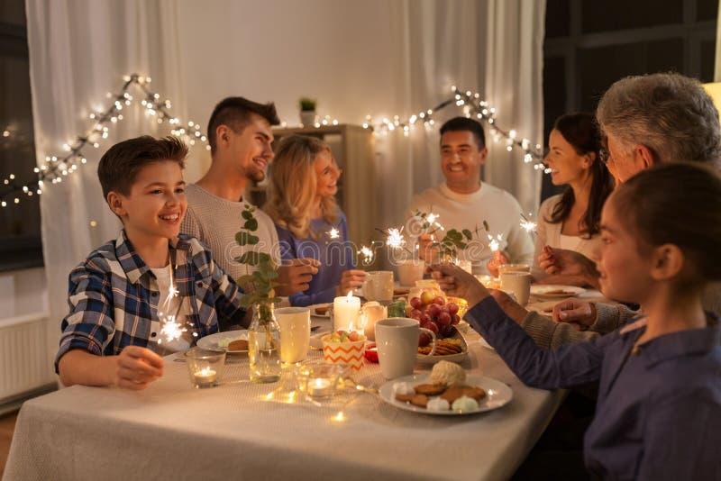 Familia con las bengalas que tienen partido de cena en casa foto de archivo