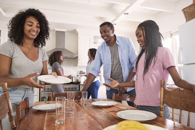 Familia con las hijas adolescentes que ponen la tabla para la comida en cocina fotografía de archivo