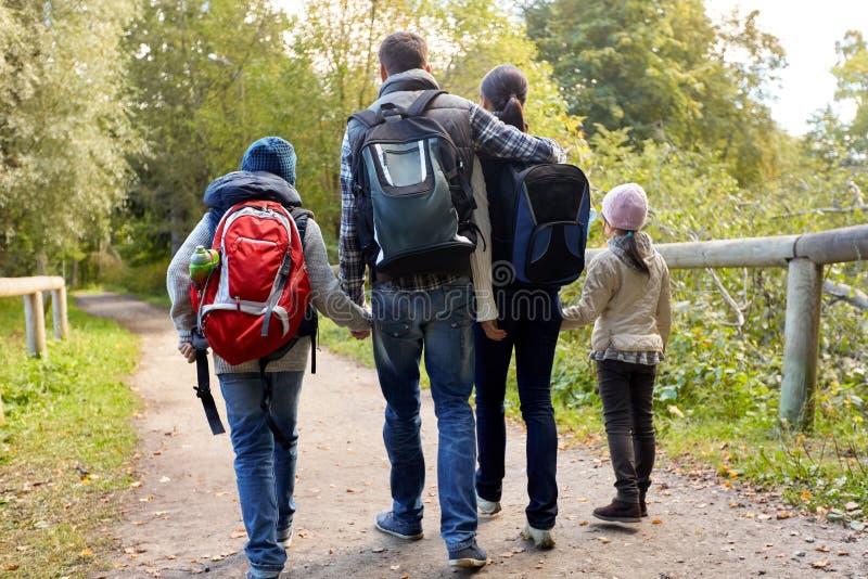 Familia con las mochilas que caminan o que caminan en bosque imagen de archivo libre de regalías