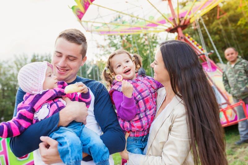 Familia con las niñas que disfrutan de tiempo en la feria de diversión fotografía de archivo libre de regalías