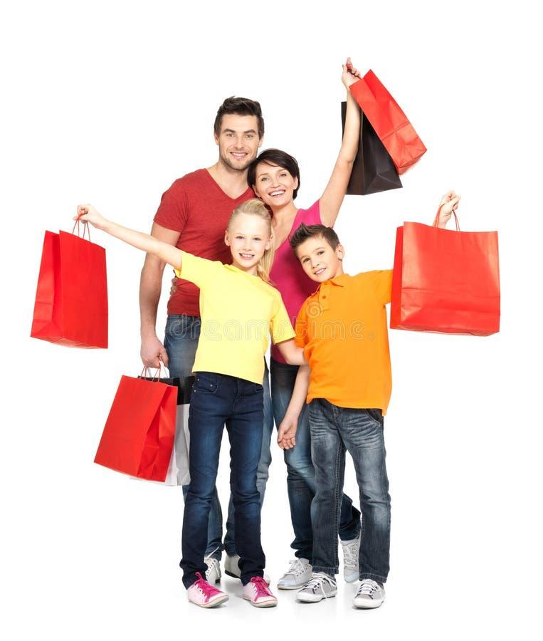 Familia con los bolsos de compras que se colocan en el estudio foto de archivo libre de regalías