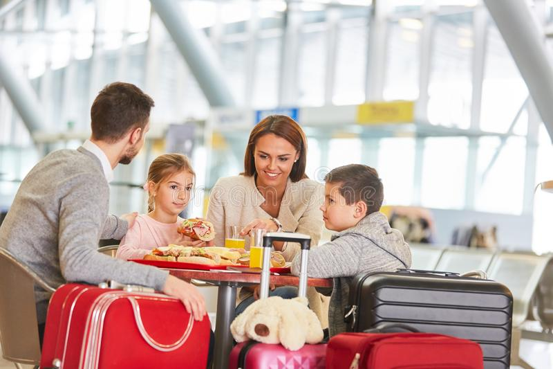 Familia con los niños en el restaurante en el aeropuerto fotografía de archivo