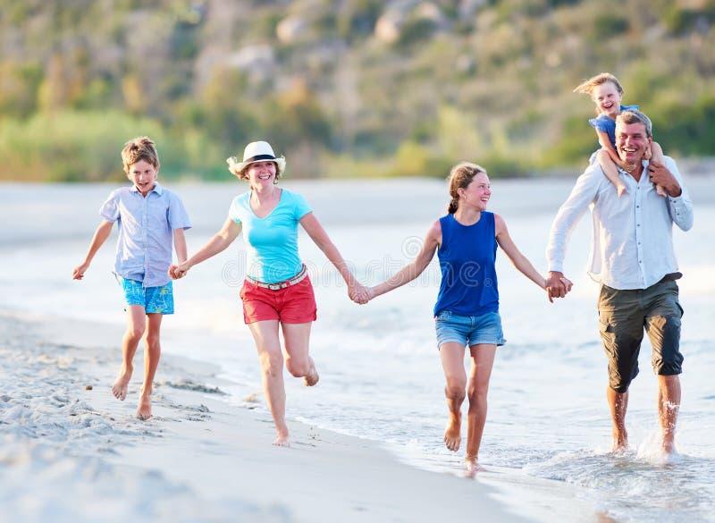 Familia con los niños en las vacaciones de verano en la playa del mar foto de archivo