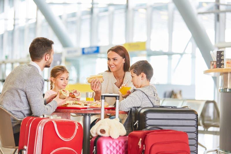 Familia con los niños que tienen comida en restaurante del aeropuerto imagenes de archivo