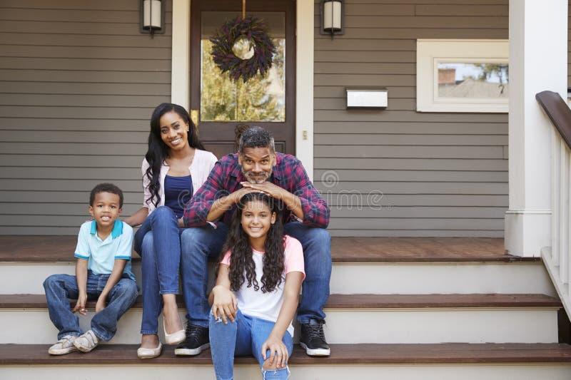 Familia con los niños Sit On Steps Leading Up al pórtico del hogar fotos de archivo