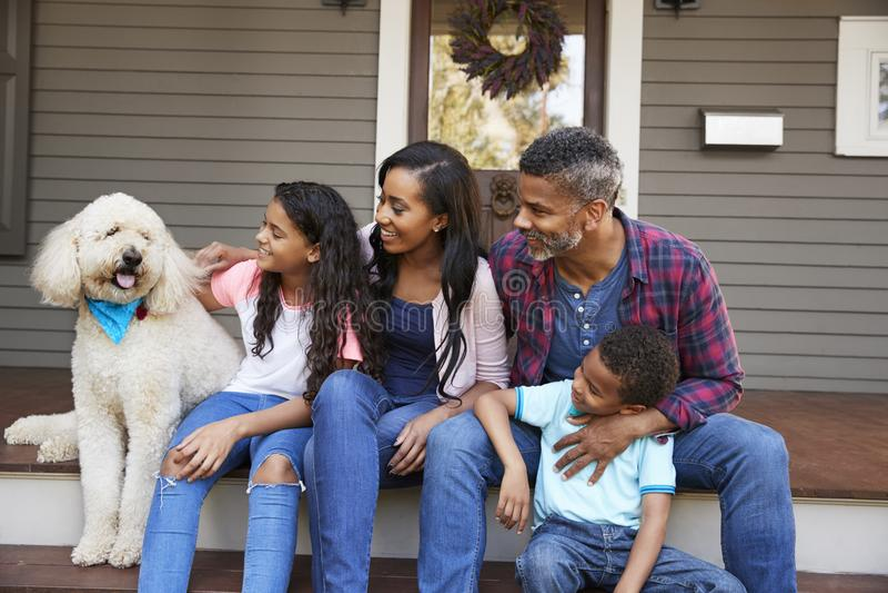 Familia con los niños y el perro casero Sit On Steps Of Home fotos de archivo libres de regalías