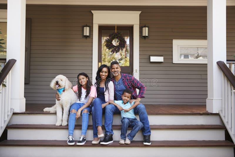 Familia con los niños y el perro casero Sit On Steps Of Home imagen de archivo