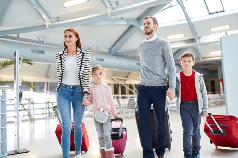 Familia con los niños y las maletas en el aeropuerto imagenes de archivo