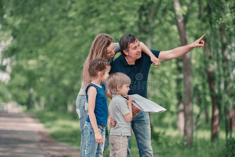 Familia con los ni?os que discuten la ruta del viaje en el mapa imagen de archivo libre de regalías