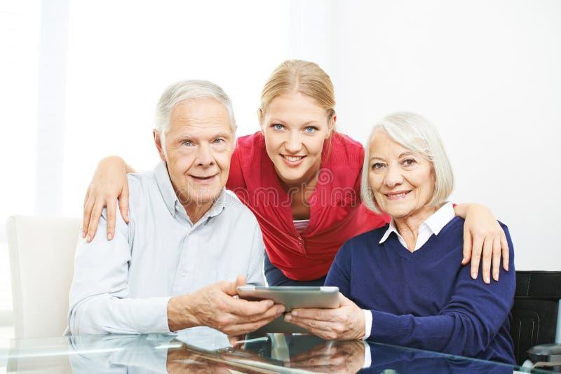 Familia con los pares y la tableta mayores imagen de archivo libre de regalías