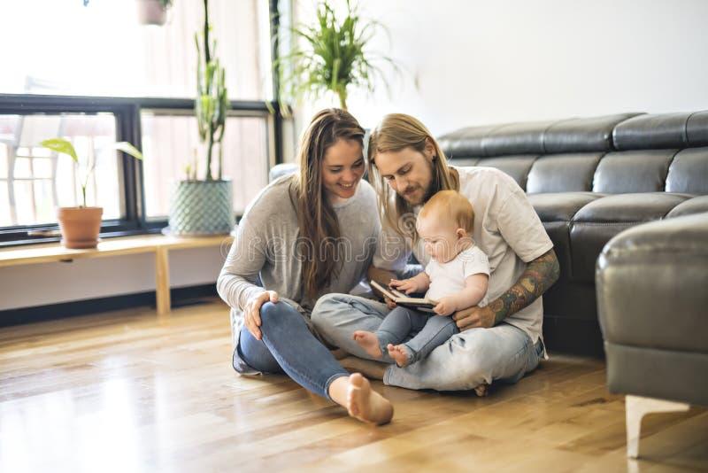 Familia con su bebé y un libro en la sala de estar foto de archivo