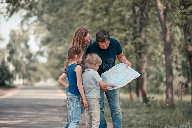 Familia con sus ni?os que discuten la ruta en el mapa fotografía de archivo