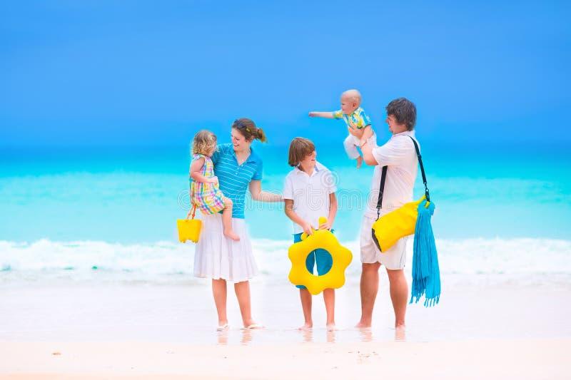 Familia con tres niños en una playa tropical fotos de archivo