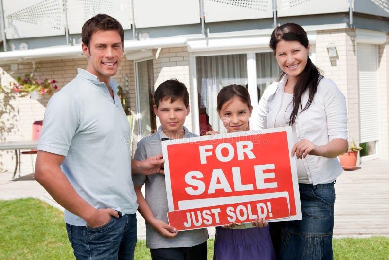 Familia con una muestra de la venta fuera de su nuevo hogar fotos de archivo