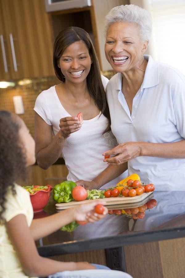 Familia de 3 generaciones que prepara una comida foto de archivo libre de regalías