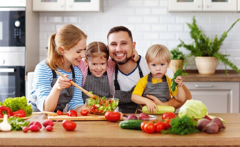 Familia de Appy con el niño que prepara la ensalada vegetal imágenes de archivo libres de regalías
