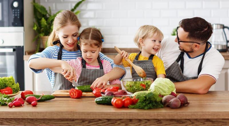 Familia de Appy con el niño que prepara la ensalada vegetal fotos de archivo