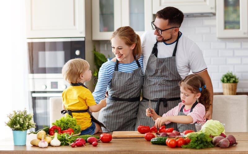 Familia de Appy con el niño que prepara la ensalada vegetal imagenes de archivo