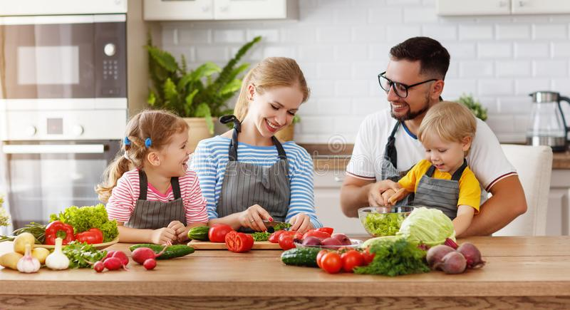Familia de Appy con el niño que prepara la ensalada vegetal imagen de archivo libre de regalías