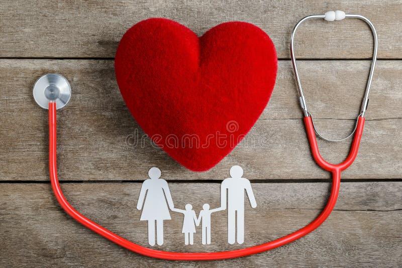 Familia de cadena roja del corazón, del estetoscopio y del papel en la tabla de madera imagen de archivo