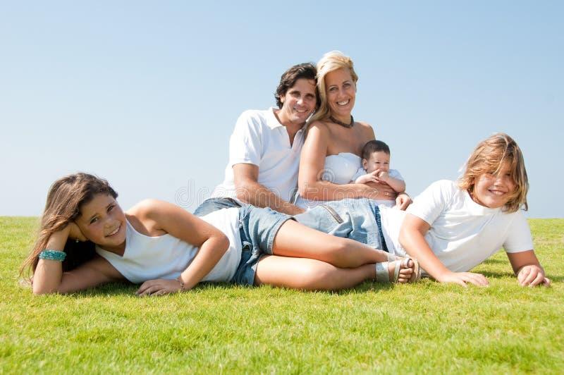 Familia de cinco que se relajan en prado imagenes de archivo