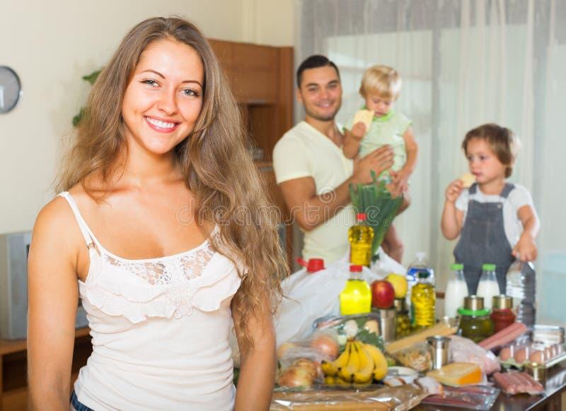Familia de cuatro miembros alegre con los bolsos de la comida foto de archivo imagen de leche - La casa de los bolsos ...