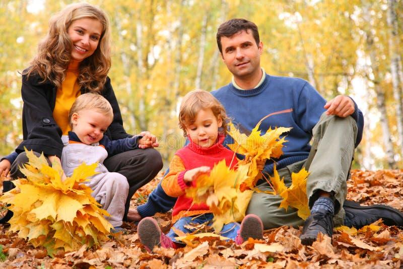 Familia de cuatro miembros con las hojas de arce amarillas en madera fotografía de archivo libre de regalías