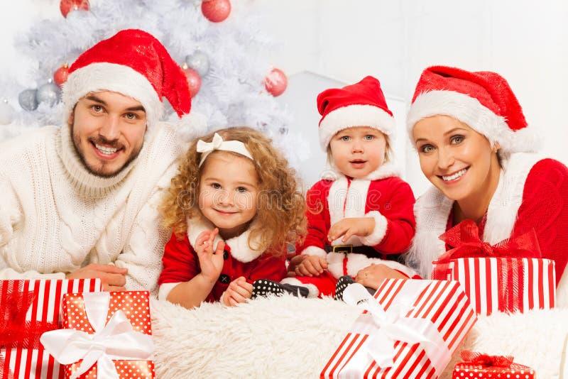 Familia de cuatro miembros con los presentes y el árbol de navidad imágenes de archivo libres de regalías