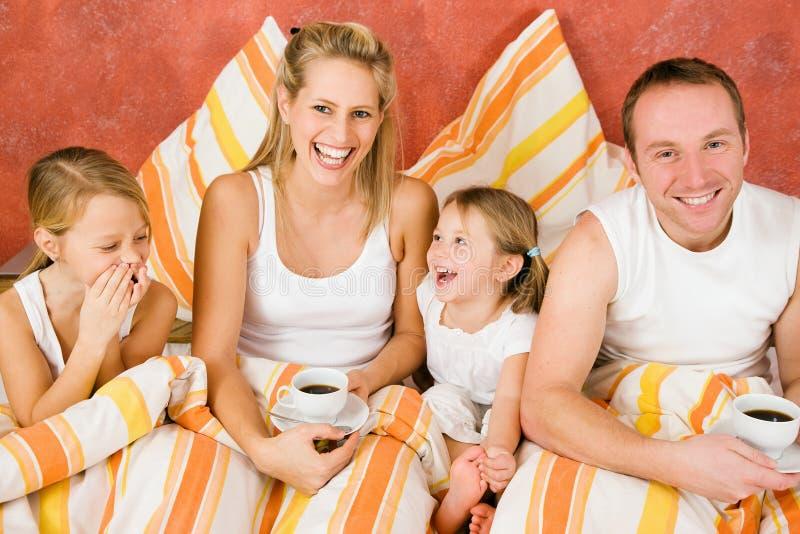 Familia de cuatro miembros en la cama que desayuna foto de archivo libre de regalías