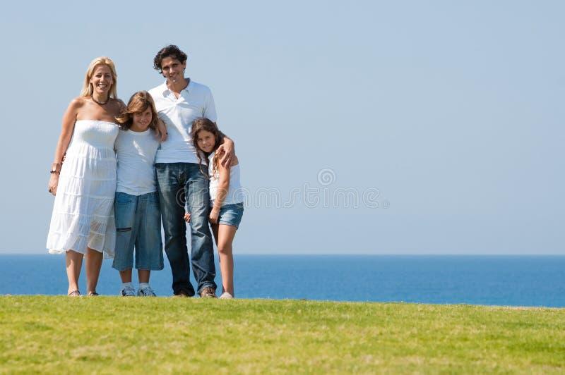 Familia de cuatro miembros en prado foto de archivo libre de regalías